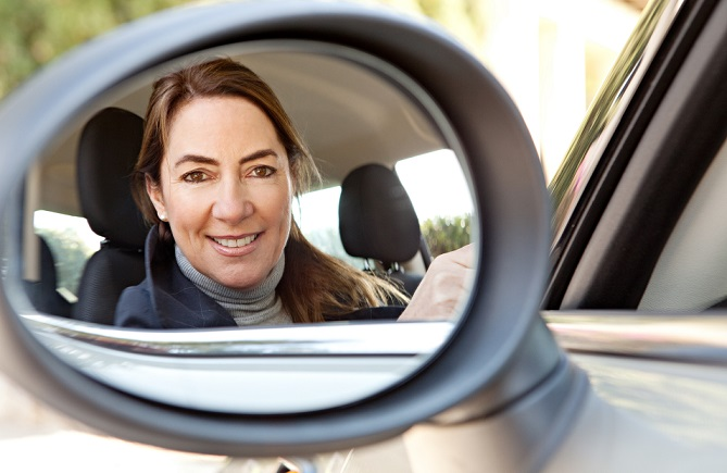 woman-looking-into-car-mirror
