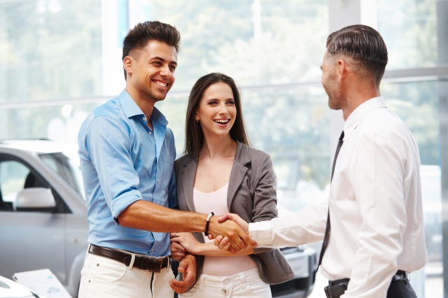 Couple shaking hands with car dealer on extended warranty