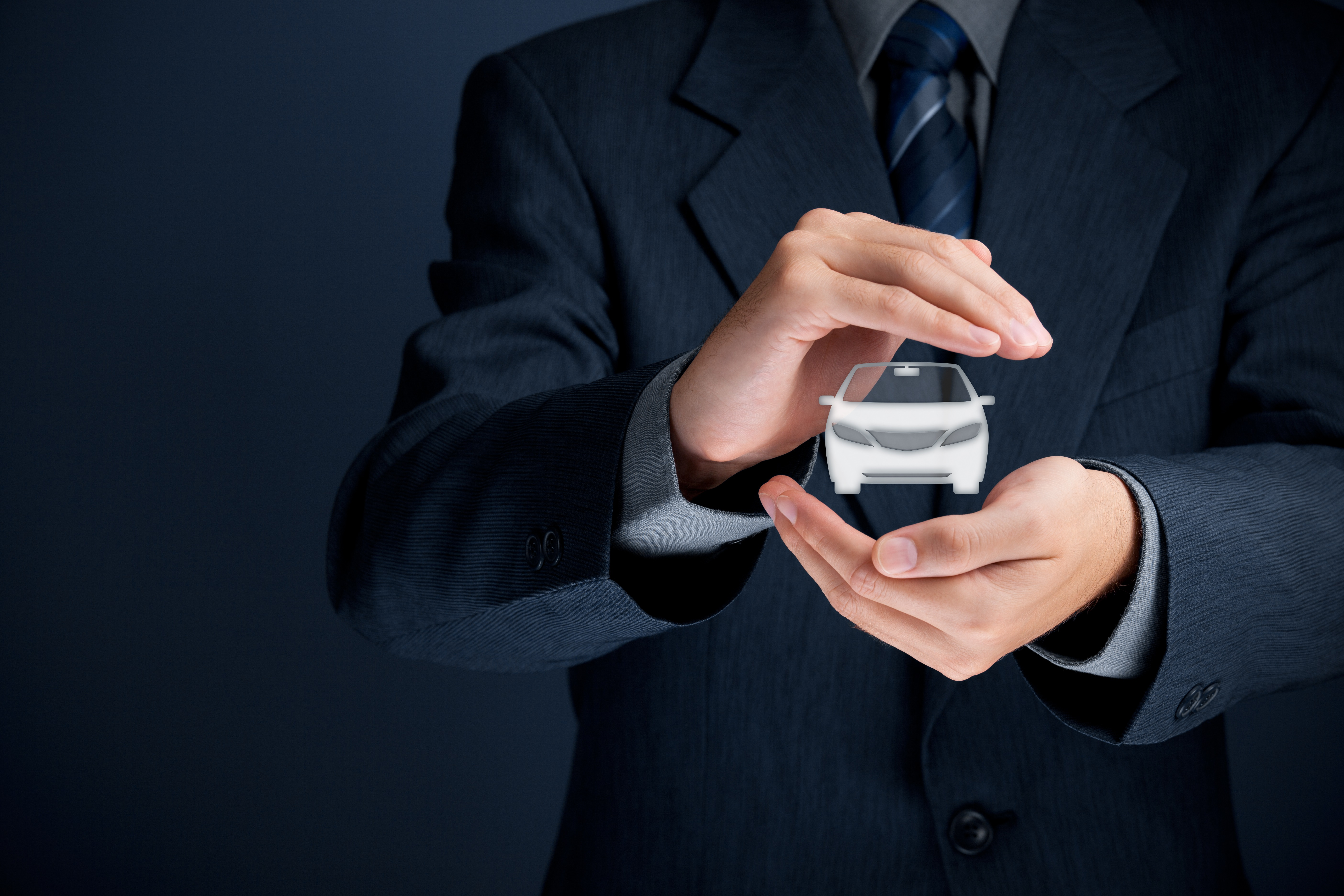 Man in suit holding miniature car