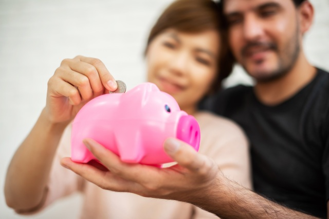 Couple saving in piggy bank