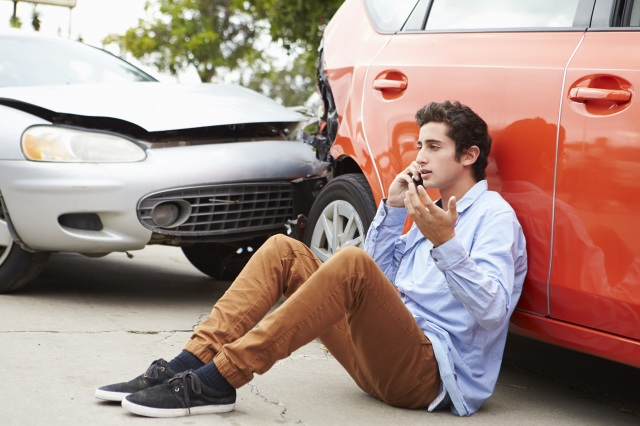 Young man on phone and wrecked car