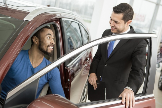 Car shopper sitting in vehicle talking to salesman