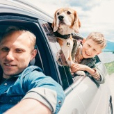 Man and boy traveling with a dog in car