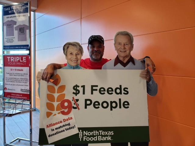 Volunteer standing with food bank cutout