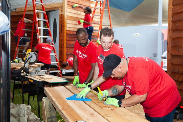 Volunteers measure siding for tiny houses for veterans