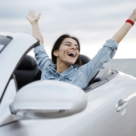 http://Woman%20waving%20from%20convertible