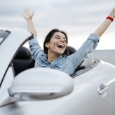 Woman waving from convertible