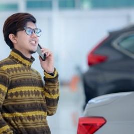 Man car buying on phone in showroom
