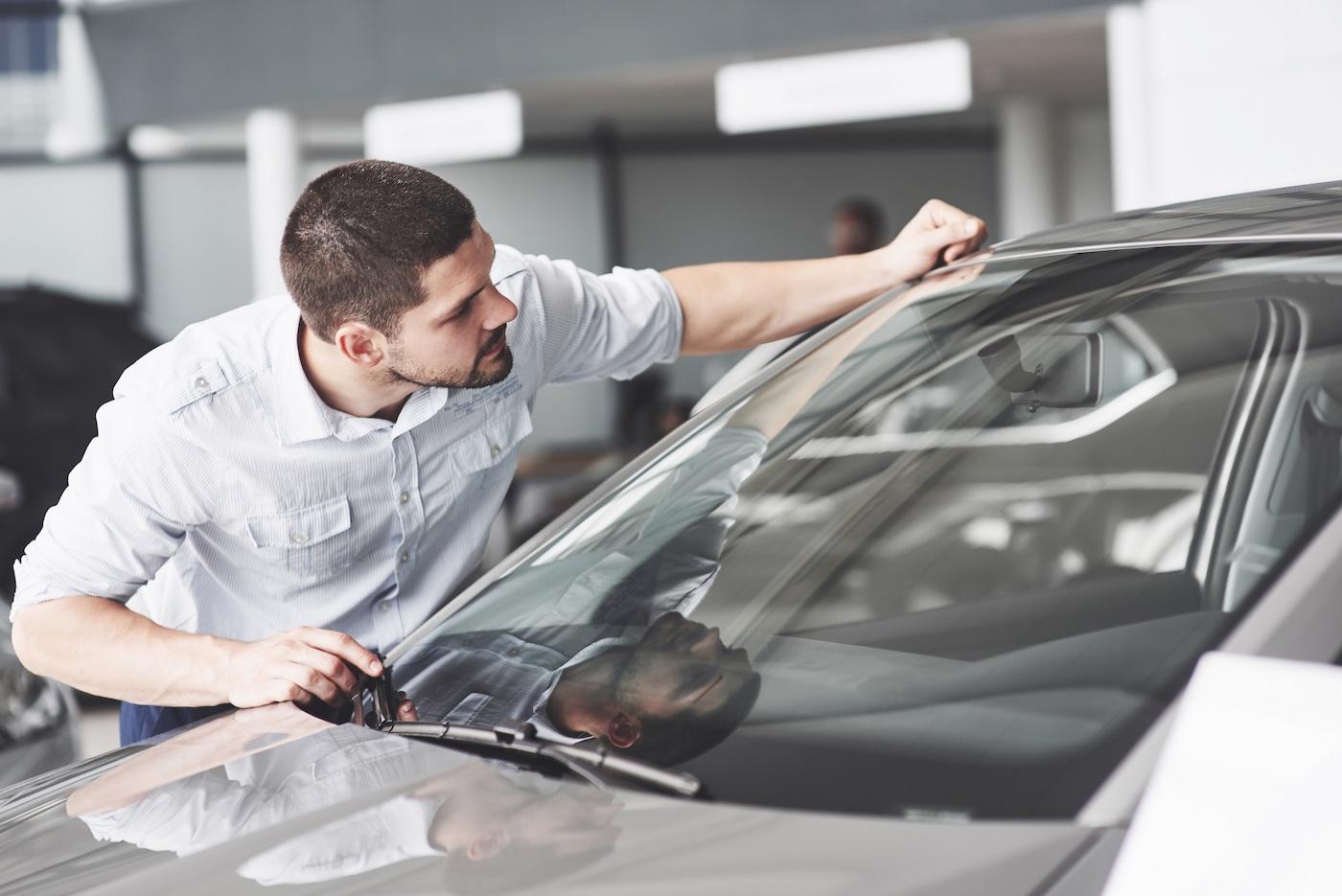 Car shopper looking at window sticker