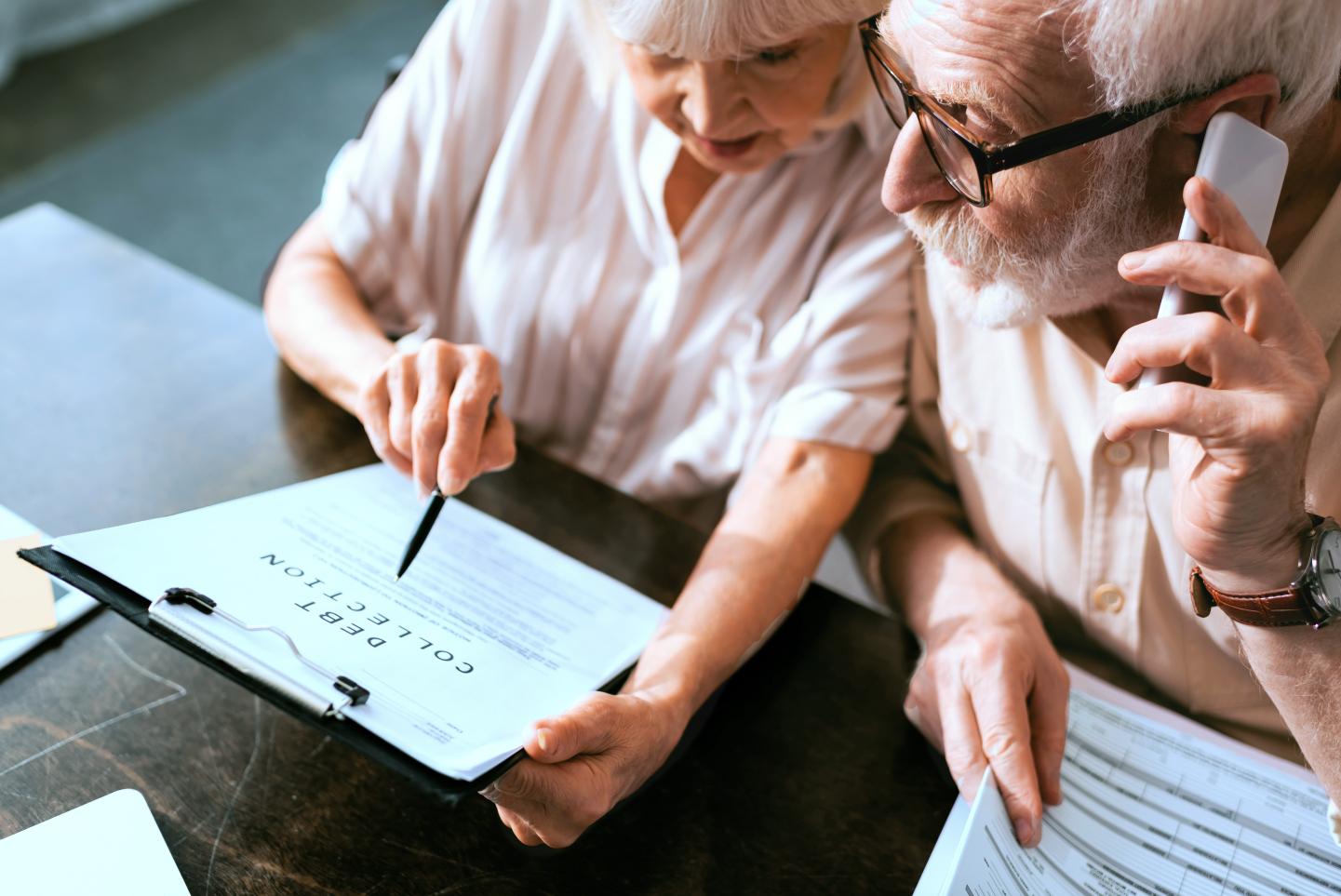 Elderly man on phone, woman holding paperwork