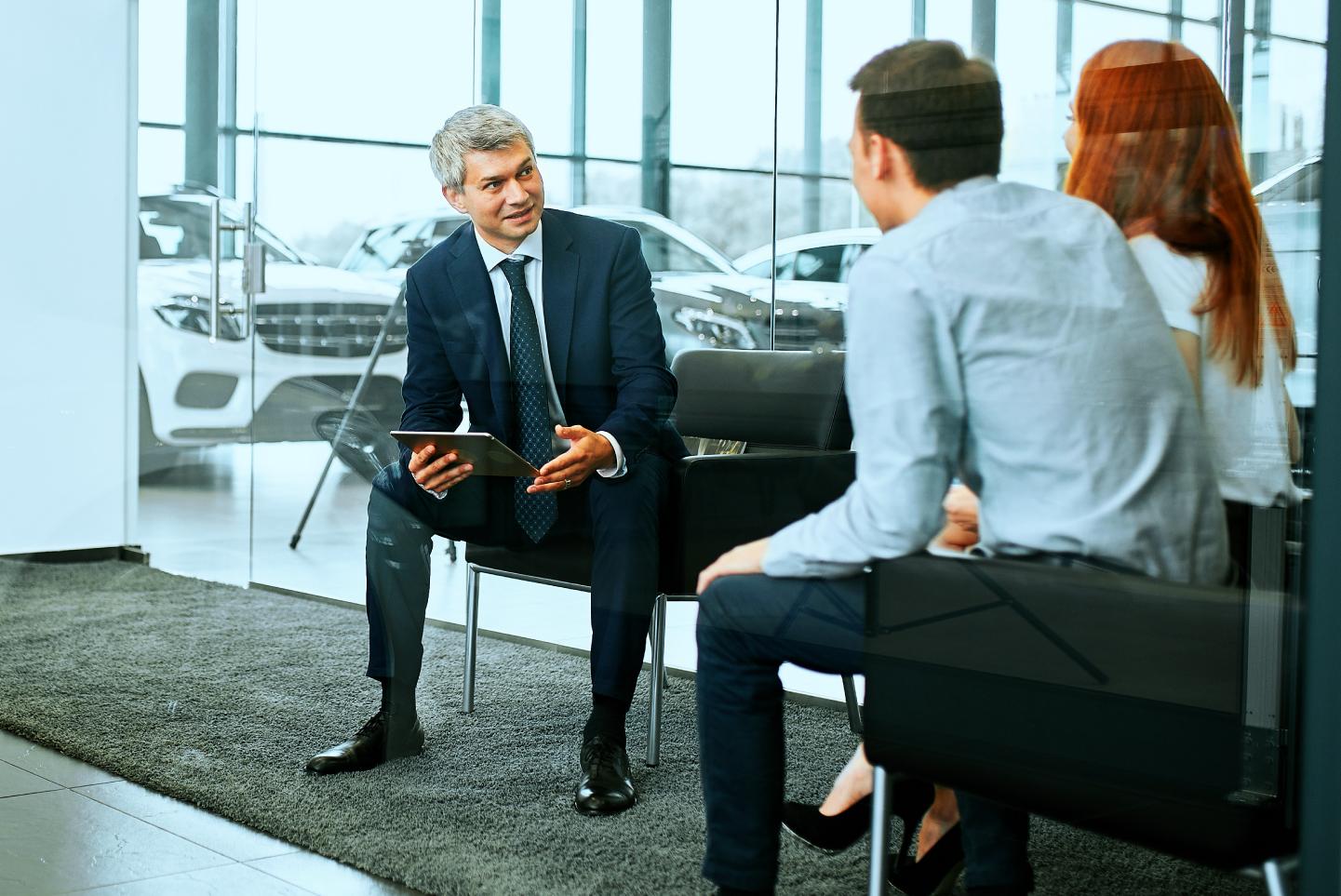 Couple talking to dealership representative